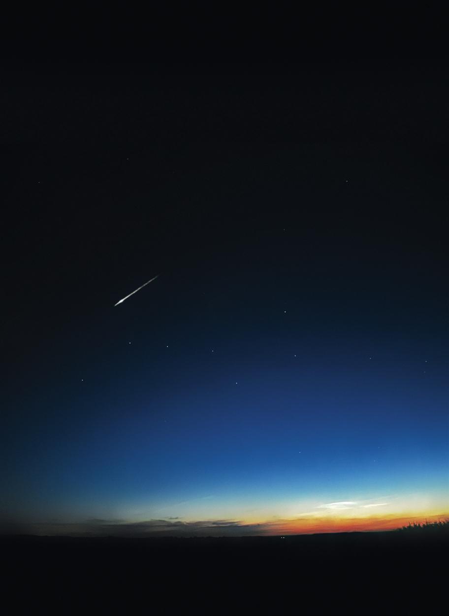 Stjernebilledet Karlsvognen eller Store Bjørn. Sensommerhimlen bliver aldrig helt mørk, over horisonten ses mørke skyer samt lysende natskyer (se side 17). Et kraftigt stjerneskud brænder op i atmosfæren, lige over Karlsvognen. (Jesper Grønne) astronomisk.dk
